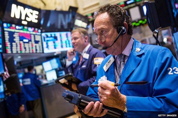 A man stands looking at computer screens at the NYSE