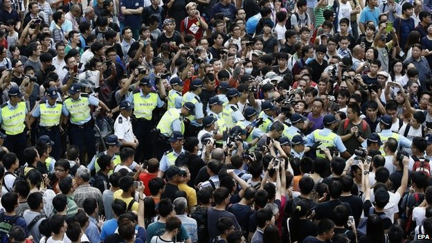 Hong Kong police officers clear the area as they arrest an anti-Occupy Central protester in Mong Kok, Hong Kong - 4 October 2014