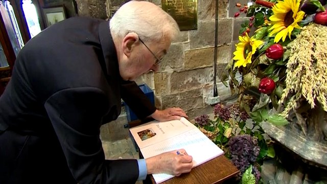 People sign a book of condolence at Eccles Parish Church