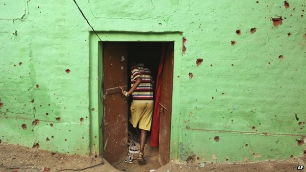 """An Indian villager enters a door of his residence near mortar shell marks allegedly fired from the Pakistan""""s side at Masha da kothe village, in Arnia Sector near the India-Pakistan international border, 6 October 2014"""
