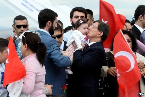 Turkish Prime Minister Ahmet Davutoglu (right) welcomed the hostages on their arrival in Ankara