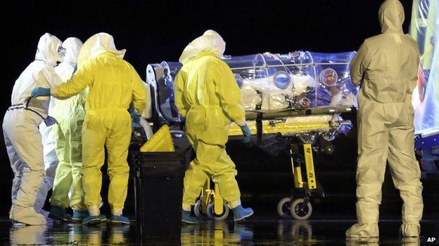 Aid workers and doctors transfer Manuel Garcia Viejo, a Spanish priest who was diagnosed with Ebola while working in Sierra Leone, from a military plane to an ambulance near Madrid, Spain, on 22 September 2014