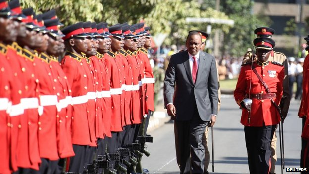 Kenya's President Uhuru Kenyatta inspects a military guard of honour on arrival for a special parliamentary session at Parliament Building in Nairobi (6 October 2014)