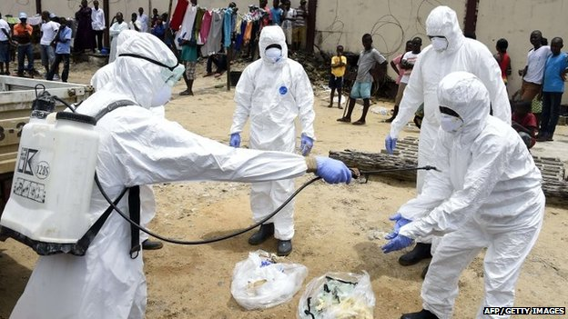 Red Cross employees in Liberia disinfect themselves