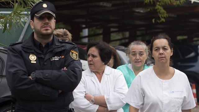 armed guard and medics outside Carols III hospital in Madrid