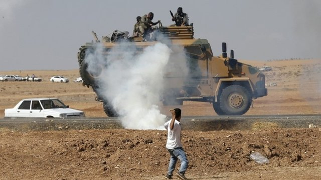 A protester throws stones at an armoured army vehicle during a pro-Kurdish demonstration