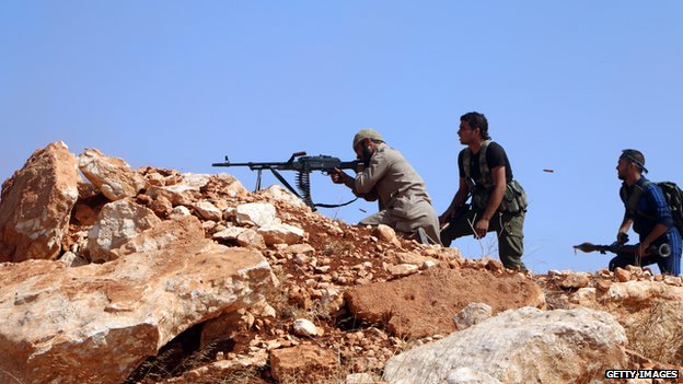 Rebel fighters fire towards Syrian government soldiers in the area of Handarat north of the northern city of Aleppo, on 3 October 2014