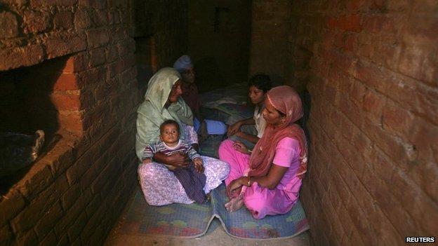 Indian villagers take shelter inside an army bunker at Devi Garh village near Jammu October 7, 2014.
