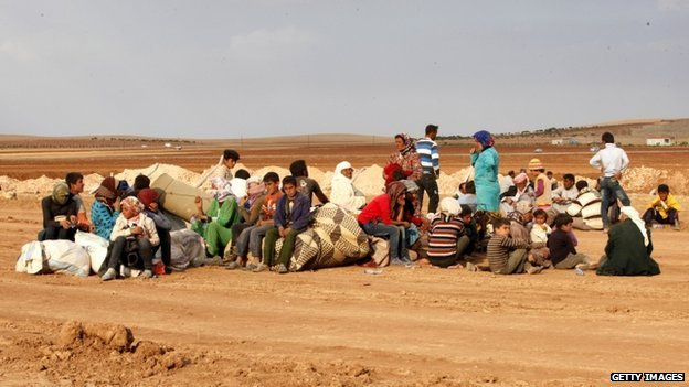 Newly arrived Syrian Kurdish refugees wait with their belongings after crossing into Turkey from the Syrian border town Kobani on 7 October 2014