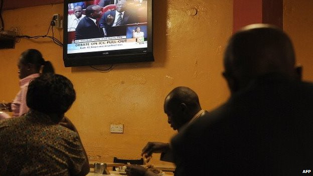 Patrons eat at a restaurant in Nairobi on 5 September 2013 as local television station broadcasts live proceedings of a parliament discussion on pulling out of the International Criminal Court (ICC)
