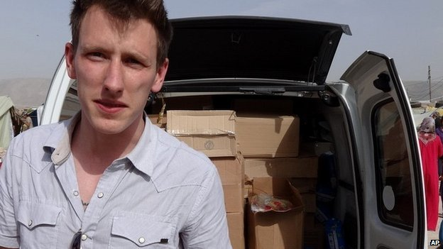 Undated photograph of Peter Kassig standing in front of a truck filled with supplies for Syrian refugees