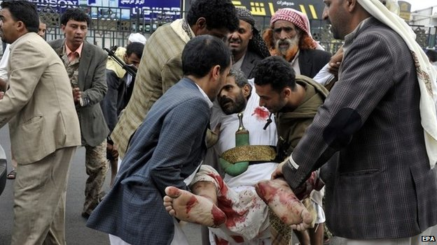 Man carry a man injured in a suicide bomb attack in Yemen's capital, Sanaa (9 October 2014)