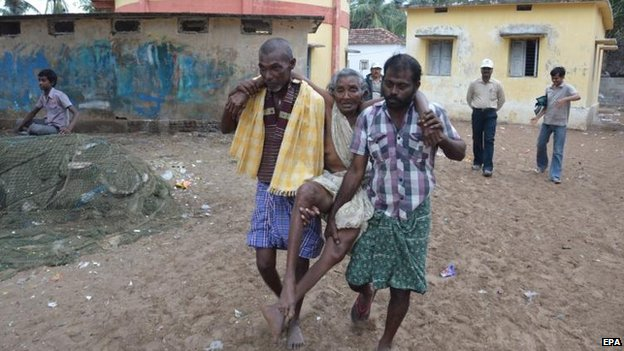 An elderly woman is carried to a relief camp in Kakinada, Andhra Pradesh