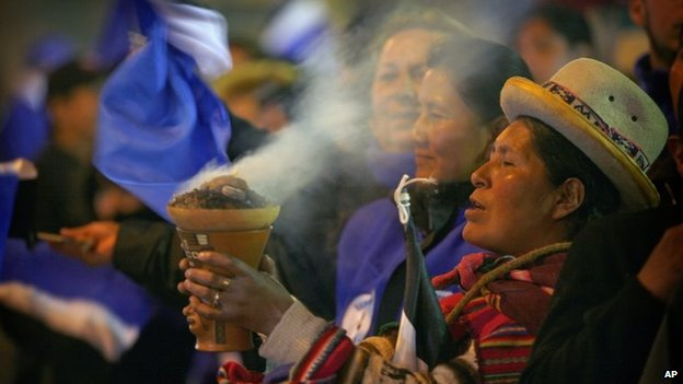 An Aymara indigenous woman burns incense in celebration as supporters wait for President Evo Morales outside the presidential palace in La Paz on 12 October, 2014.