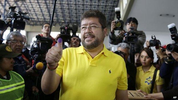 Samuel Doria Medina shows his finger after casting his ballot at a polling station in La Paz on 12 October 2014