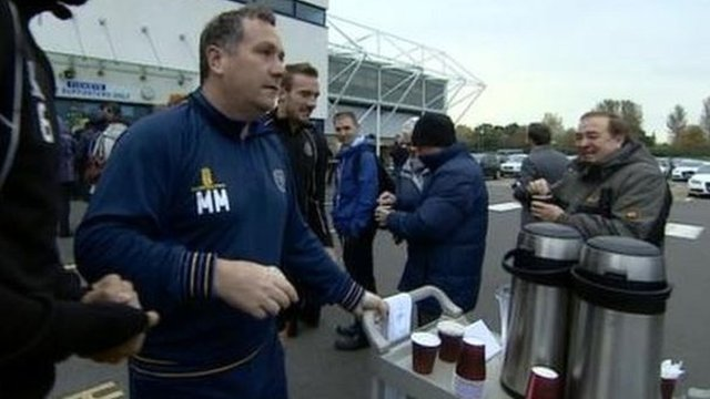 Shrewsbury Town manager Micky Mellon serves up cups of tea to queuing fans at the Meadow