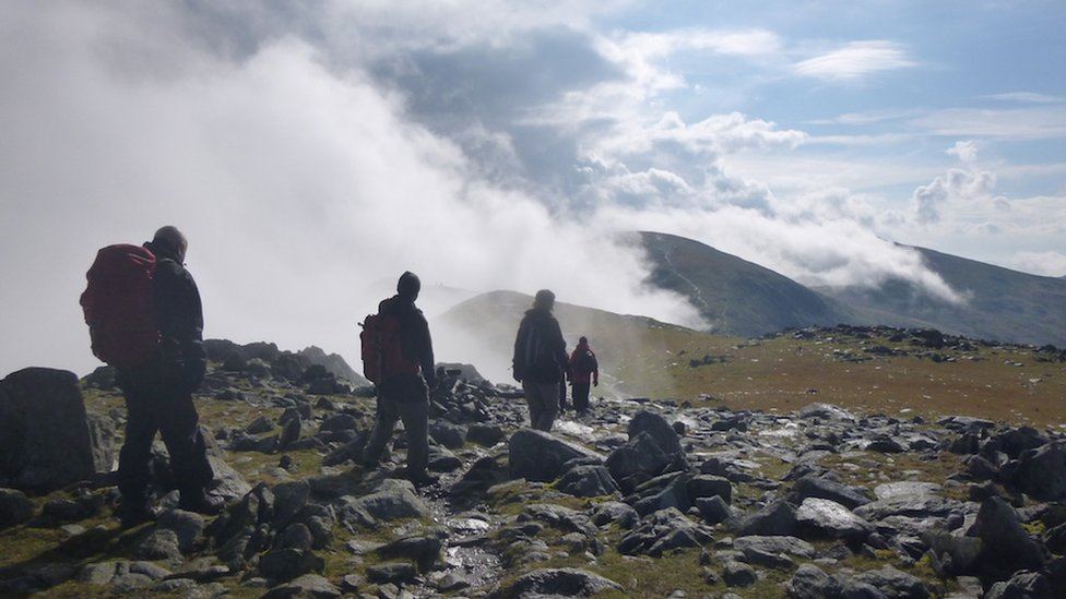 Mountain trekkers walking through rocks to a cloudy horizon on the Old Man of Coniston in the English Lake District.