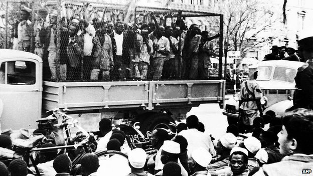 """Some of the hundreds of Mau Mau suspects who were rounded up in Nairobi, Kenya, on 21 October 1952, are taken away for interrogation in a police """"cage""""."""