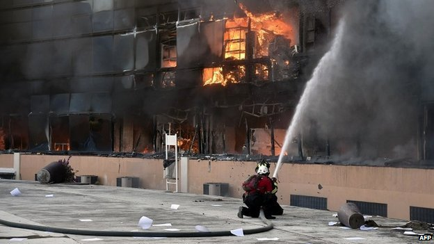 Firefighters attempt to extinguish a fire at the Guerrero state capital building in Chilpancingo, Mexico - 13 October 2014