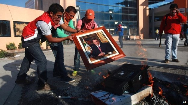 Students burn a portrait of Guerrero Governor Angel Aguirre before setting fire to the state capital building in Chilpancingo, Mexico - 13 October 2014