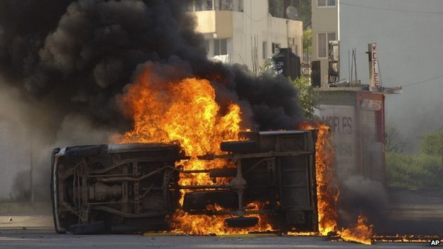 An overturned car burns after it was set on fire by protesting college students outside the Guerrero state capital building in Chilpancingo, Mexico - 13 October 2014