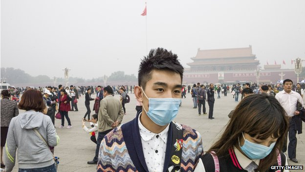 A couple wearing face masks visits Tiananmen Square in Beijing on 11 October, 2014