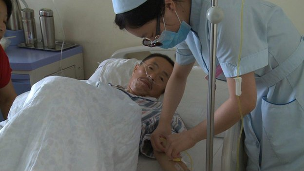 A nurse treats a patient in a Chinese cancer hospital