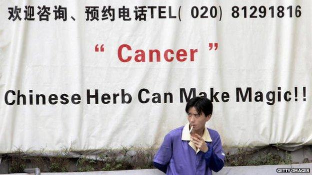 A Chinese man enjoys a cigarette as he rests against a poster advertising a cure for cancer, in Guangzhou, southern China's Guangdong province on 15 June 2012