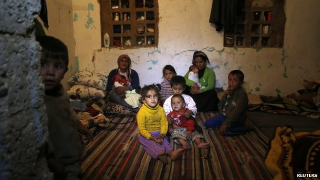 Syrian refugees from Kobane sit in a room in the south-eastern Turkish town of Suruc (13 October 2014)