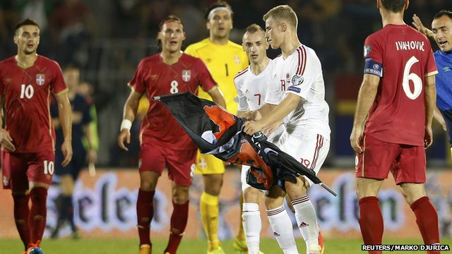 Balaj of Albania takes a flag depicting so-called Greater Albania which was flown over the pitch during their Euro 2016 Group I qualifying soccer match against Serbia at the FK Partizan stadium in Belgrade