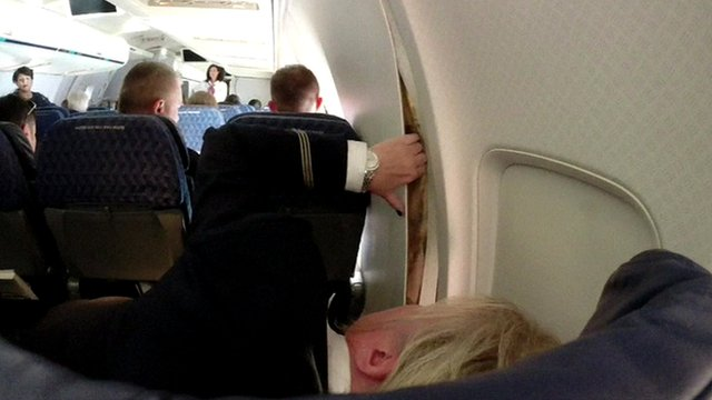 Flight attendant looks at crack in plane wall