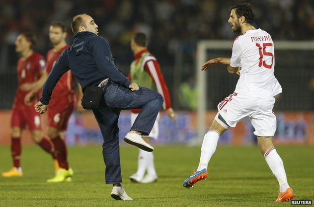 A Serbia fan confronts an Albanian player in the stadium in Belgrade, 14 October
