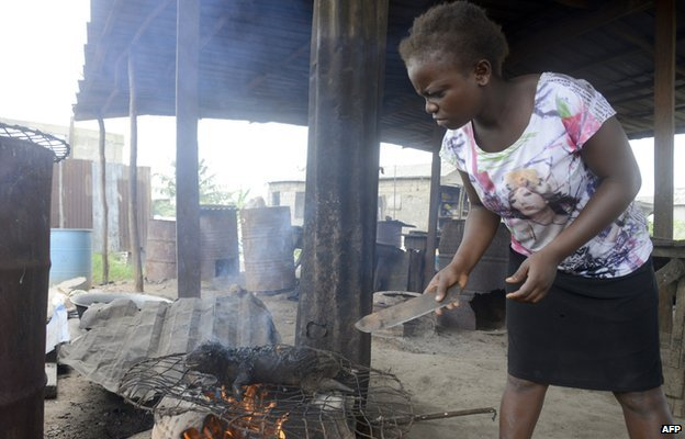 woman roasts bushmeat