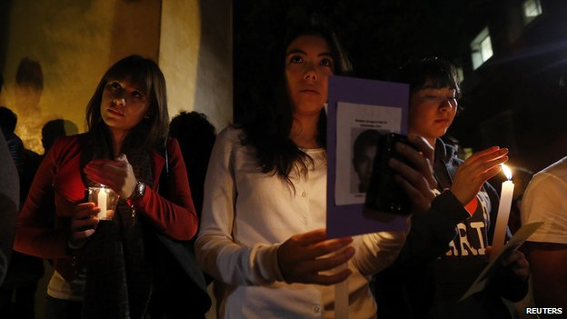 People hold candles during a vigil for the 43 students