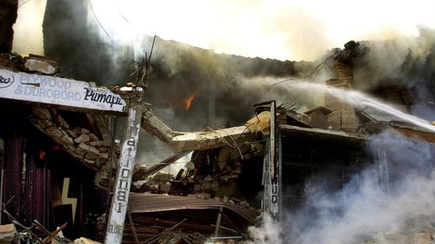 A destroyed two-story Bank of Rajasthan buidling is seen on fire near Jullundur, India, Friday May 3, 2002, after an Indian Air Force MiG-21 jet crashed into the building.