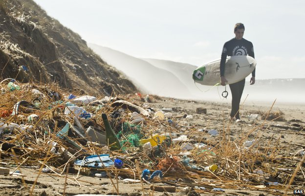Surfer walking on the beach past litter