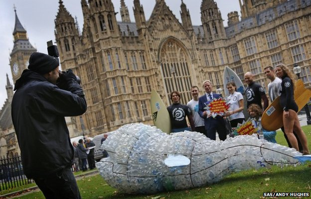 People standing outside Parliament with a whale made out of plastic bottles