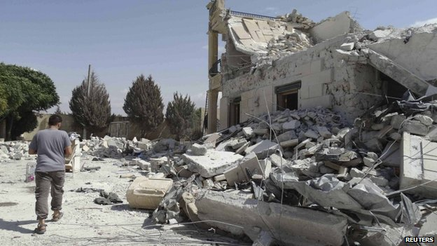 A man walks past a damage building in Aleppo on 27 September 2014