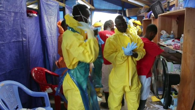 Healthcare workers putting on protective clothing