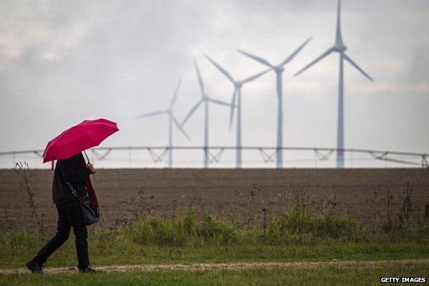 Woman with umbrella walks past wind turbines