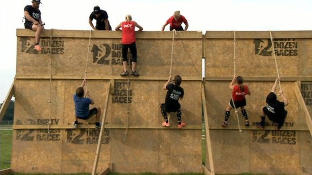 People climbing over wall during race