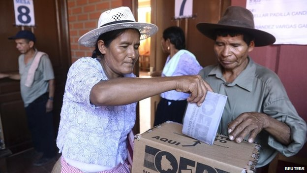 A woman deposits her ballot during the presidential election in Cochabamba on 12 October, 2014