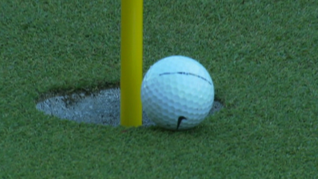 Tiger Woods chips the ball into the hole on the 16th at Augusta