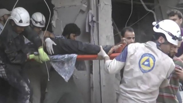 Workers in hard hats pull an injured man from a building.