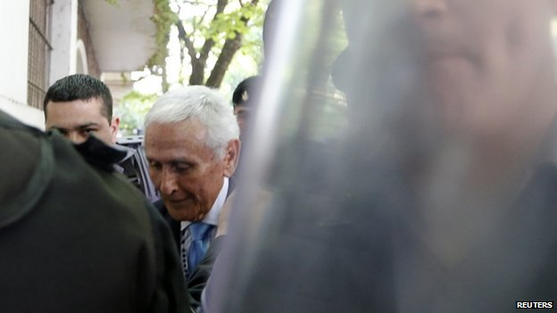 Miguel Etchecolatz (C), former Buenos Aires province's chief of police, is led into a courtroom to attend the final stage of his trial for his role in the kidnapping, murder and torture of people during Argentina's last dictatorship in La Plata on 24 October 2014.