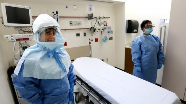 Two medical workers wear protective suits inside an isolation room appropriate to handle people inflected with the Ebola virus at Bellevue Hospital Center in New York, New York
