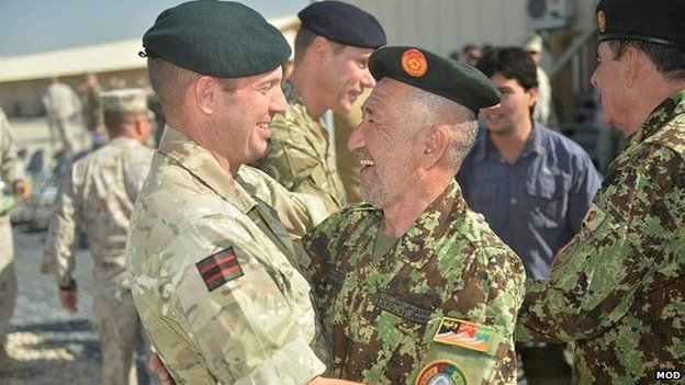 A UK soldiers hugs an Afghan soldier