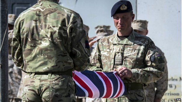 Two British soldiers hold a folded British flag