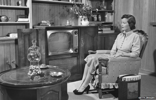 CIRCA 1950s - a black and white photograph of a woman watching television