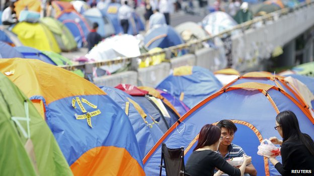 People eat lunch between tents set-up by pro-democracy protesters in a part of Hong Kong's financial central district the protesters are occupying, on 29 October, 2014